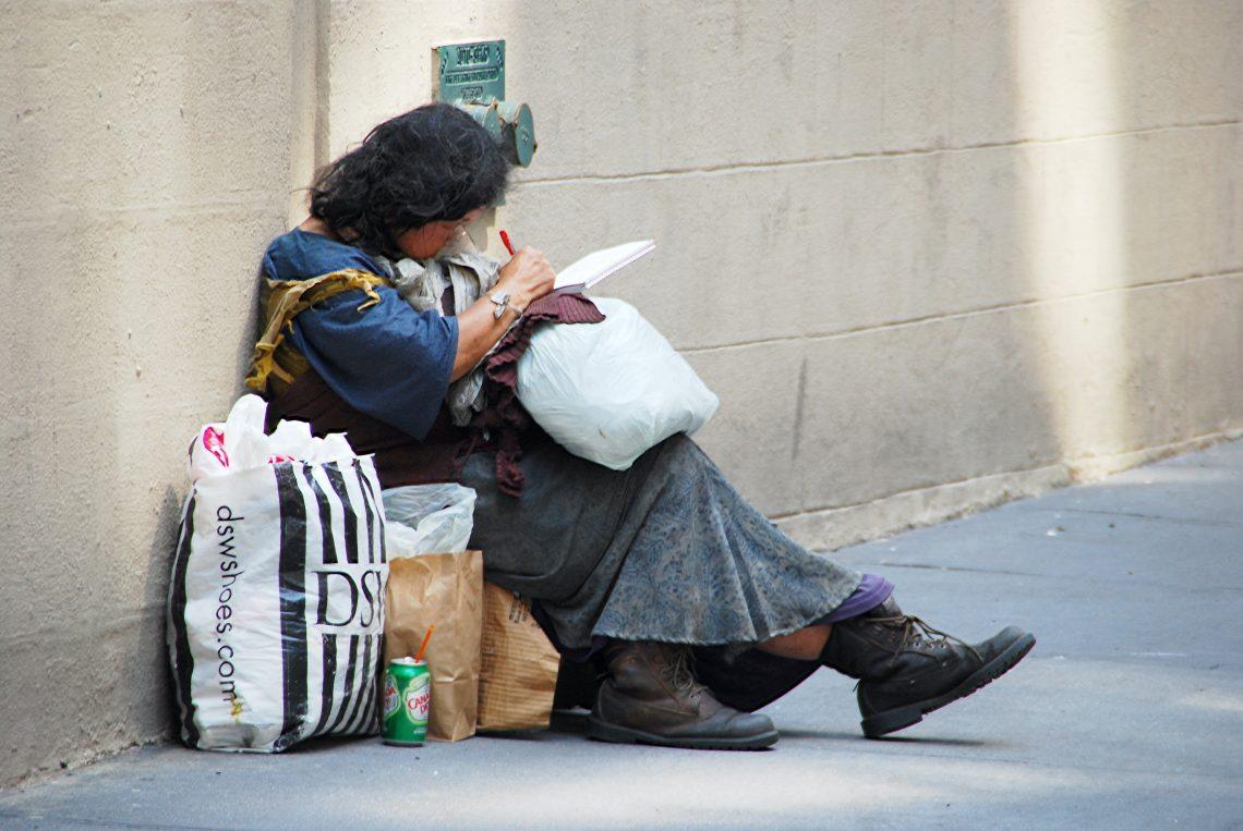 Femme itinérante assise contre un mur sur le trottoir